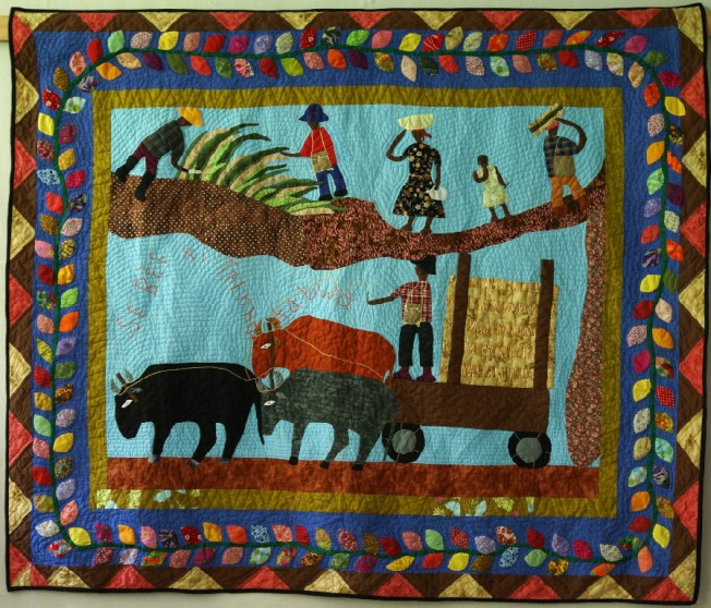 Quilt artist Denise Estavat tells the story of life in the village where she grew up.  The men cut sugar cane and the oxen pull the cart to deliver it to market.  Notice the intense echo quilting and refined details in embroidery.